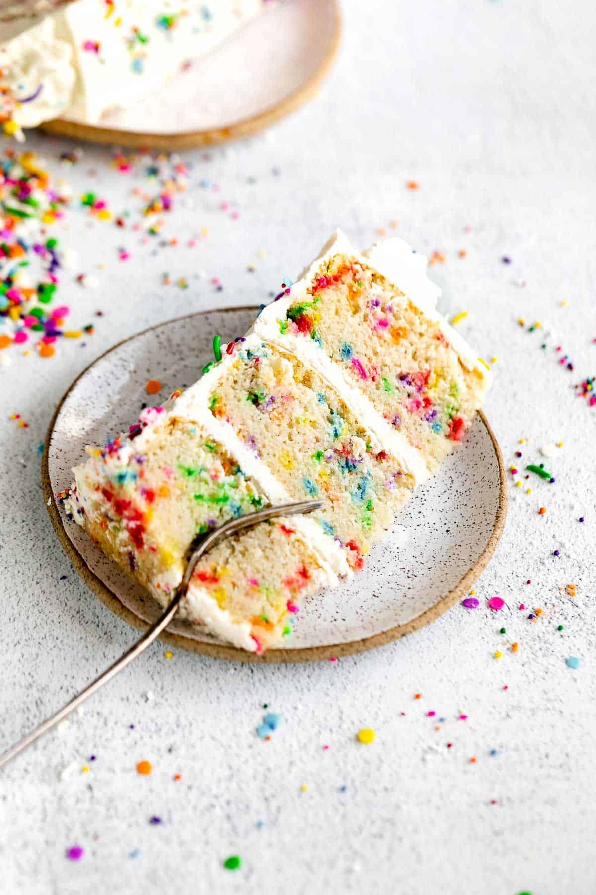 slice of three layer gluten free birthday cake with sprinkles