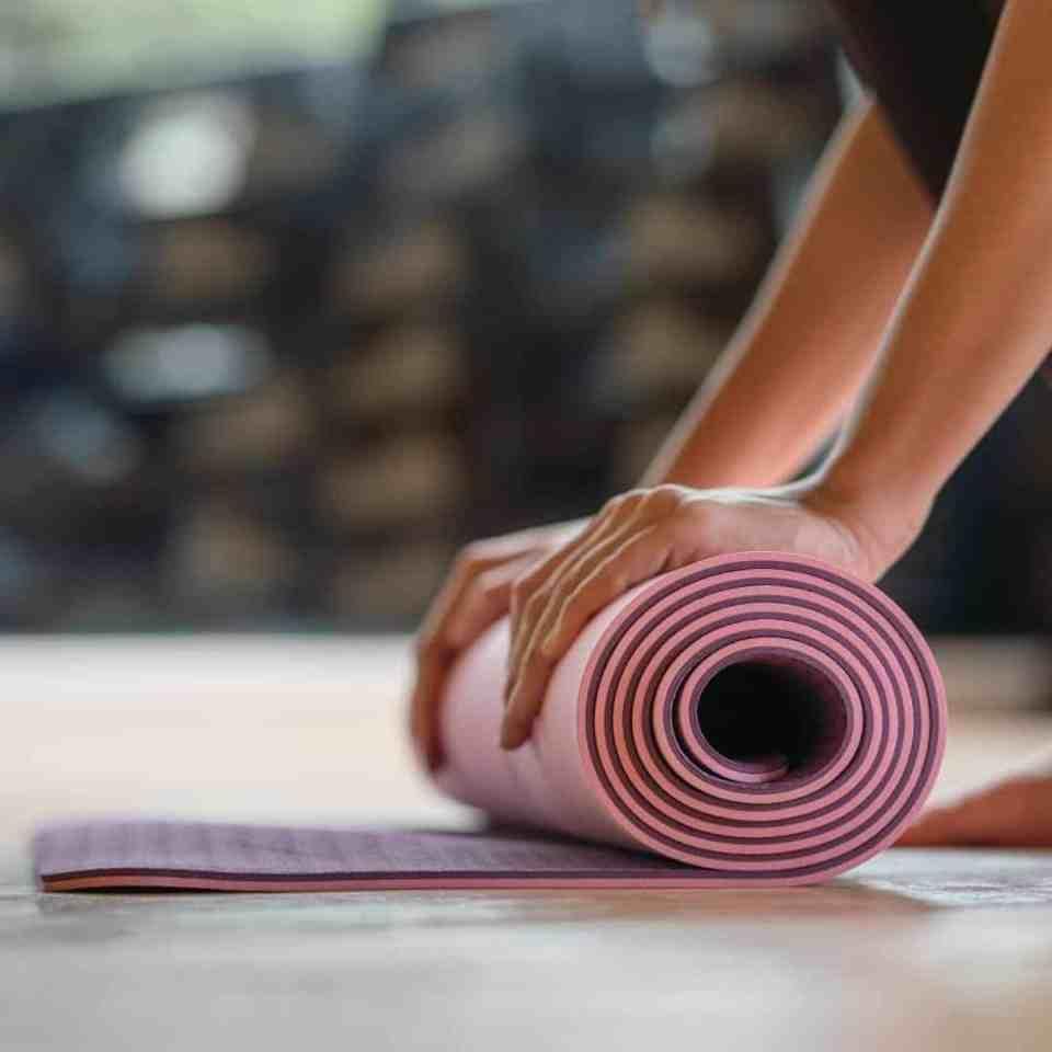 Woman rolling up a pink yoga mat after yoga meditation.