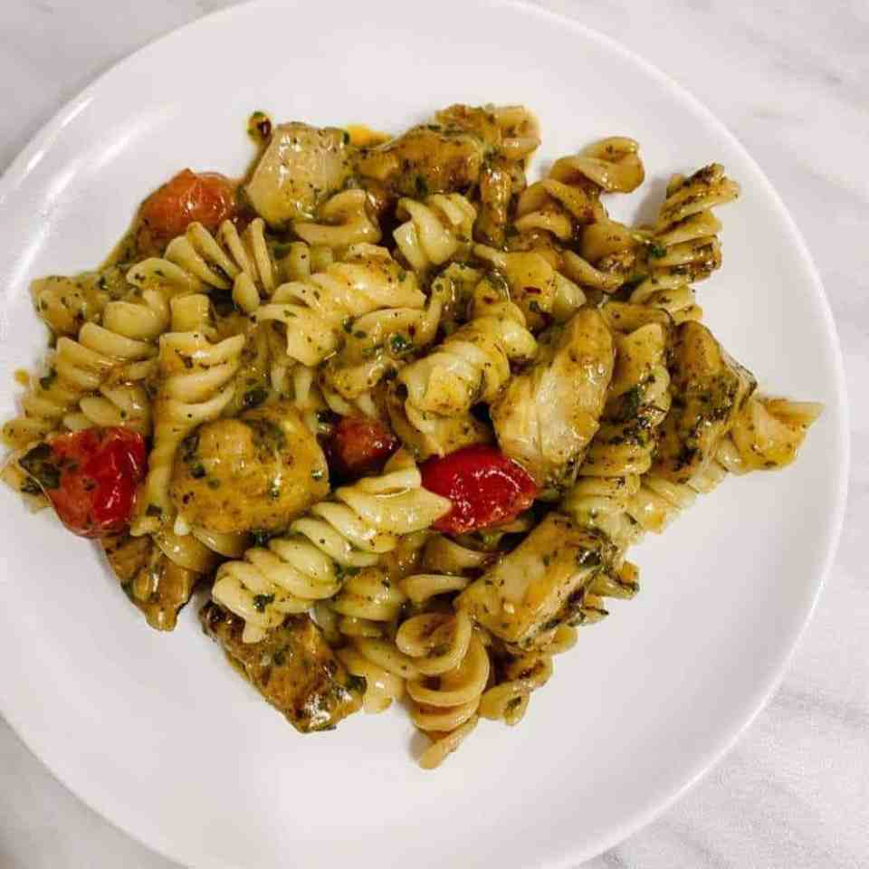 A white plate topped with healthy cajun chicken pasta.