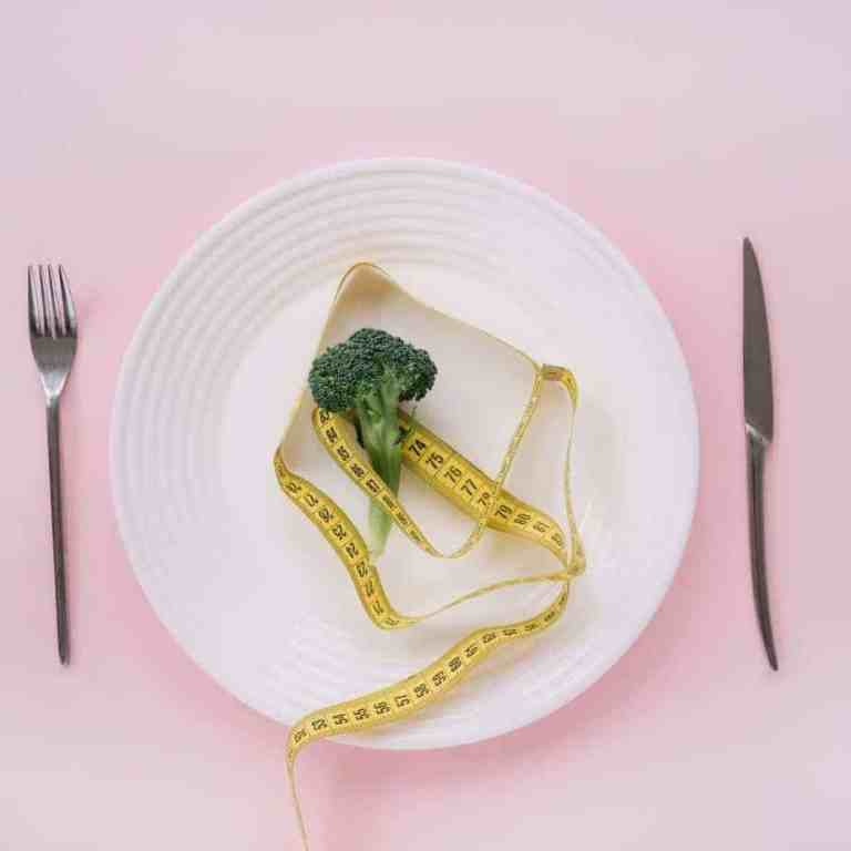 White plate with piece of broccoli and tape measure. There are simple ways to lose weight without dieting.
