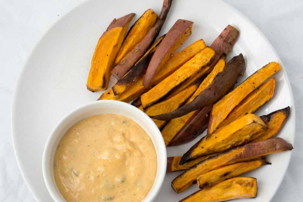 sweet potato fries in fan shape on white plate with white ramekin of spicy dairy free cashew cream sauce
