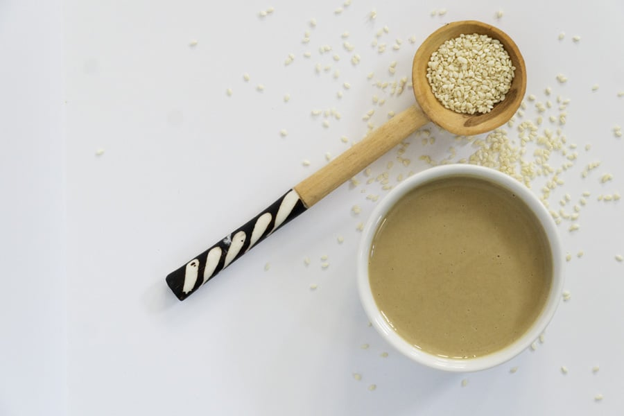 White bowl of tahini with wooden spoon overflowing with sesame seeds showing what is tahini, how it's made, tahini benefits, and how to use it.