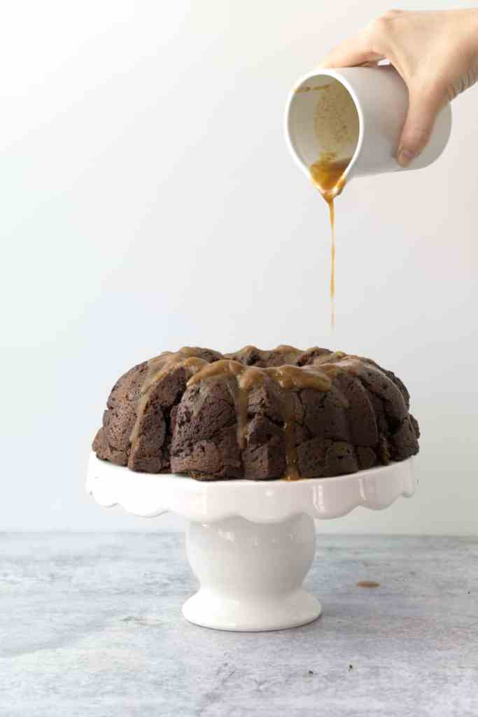 hand pouring coconut cardamom glaze onto chocolate chai bundt cake on white cake stand on cement table with white backdrop