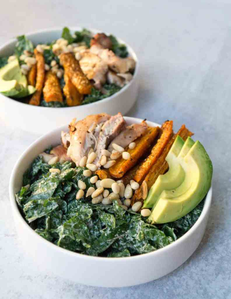 Kale tossed in creamy tahini cashew Caesar dressing topped with avocado, pine nutes, roasted carrot spears and grilled chicken thighs