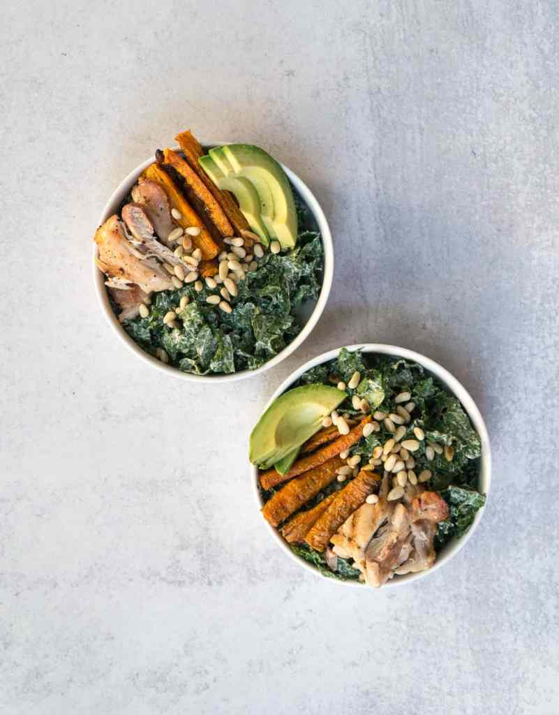 Superfood Kale Caesar salad in 2 white bowls with avocado, carrot fries, pine nuts and chicken thighs with vegan Caesar dressing