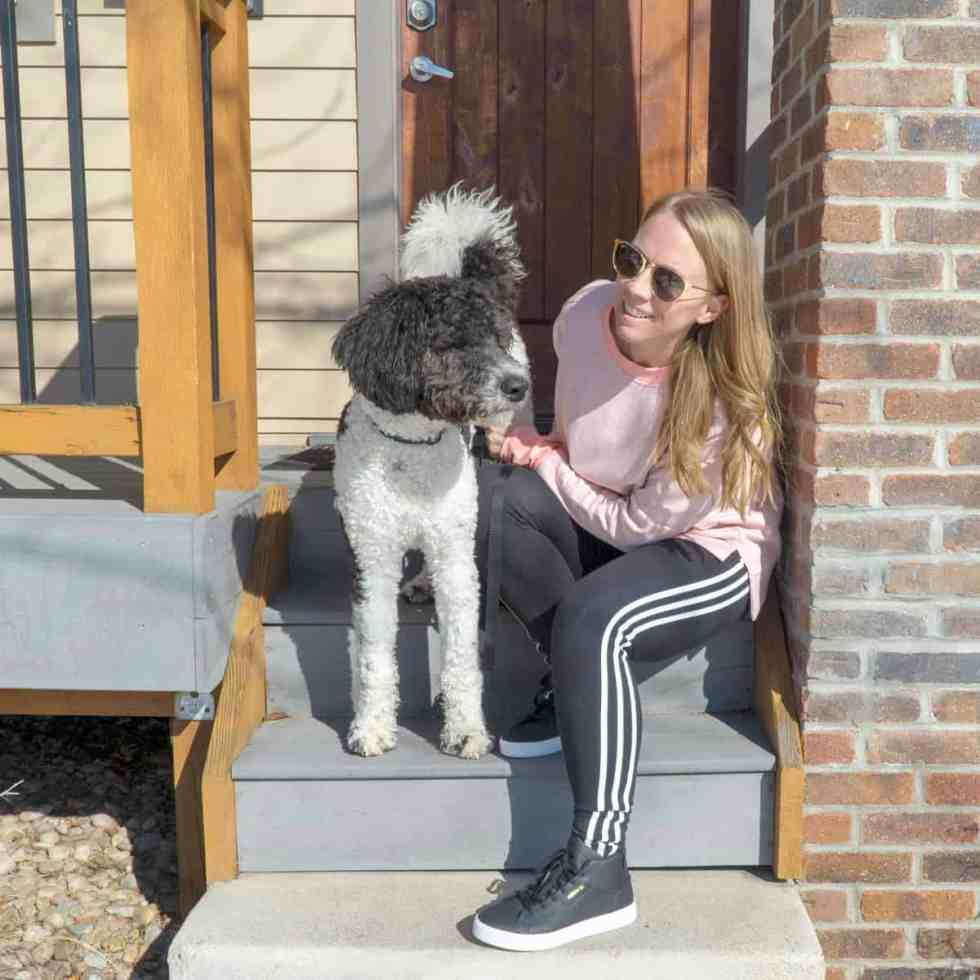 Blond girl and bernedoodle on the stairs with Adidas leggings and black sneakers and pink sweatshirt