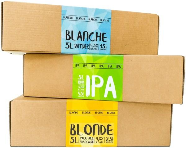 Trois recharges Eazy Brewing empilée les unes sur les autres. On peut voir les recettes pour bière Blonde, IPA et Blanche. Elles contiennent tout le nécessaire pour brasser 4 à 5 litres d'une bière .