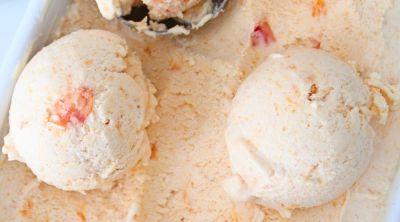 A few balls of peach ice cream in an ice cream container
