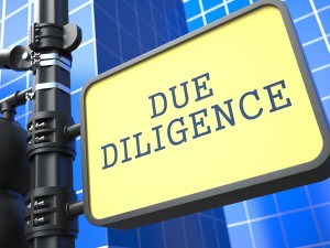 The words, Due Diligence, printed on a street sign in front of an all-glass window, high-rise building.