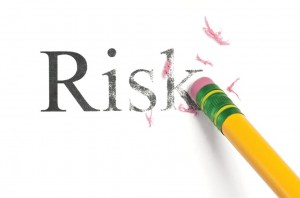 The word, Risk, being erased by a yellow pencil with a green band and eraser crumbs scattered about.