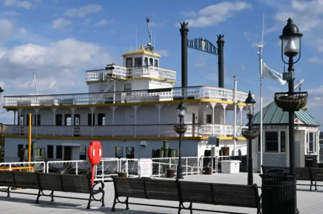 """The Cherry Blossom in the harbor of Old Town Alexandria. Built in Palatka, Florida in 1984, the vessel is an """"authentic split sternwheeler and re-creation of a 19th century Victorian riverboat. Features include ornate iron rails and a plush interior of brass and mahogany."""""""
