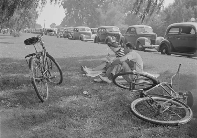 Bikers in Hains Point 1935 sitting on grass with old mobiles parked on the speedway