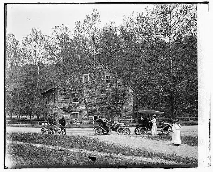 Cyclists and cars in front of Peirce Mill between 1918 and 1920