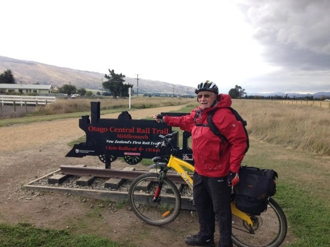An e-biker standing in front of the sign of the -bike Lovers - Otago Central Rail Trail in New Zealand.