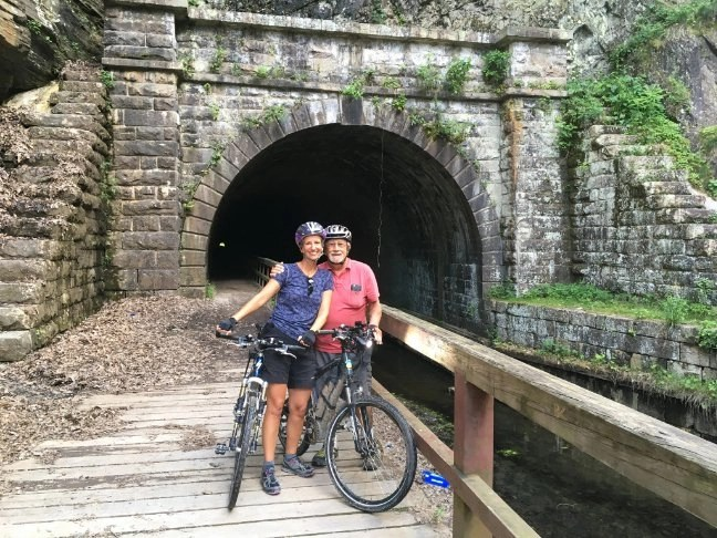 A couple of ebikers standing in front of the PawPaw tunnel on the C&O Canal rail trail.