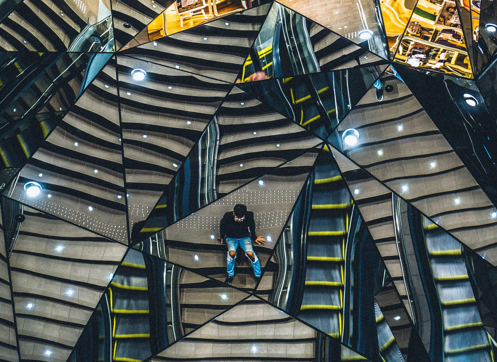 A person sits amid many triangular mirrors, fracturing the view around them.