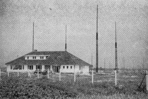 A house-like building in a rural area surrounded by 4 tall masts