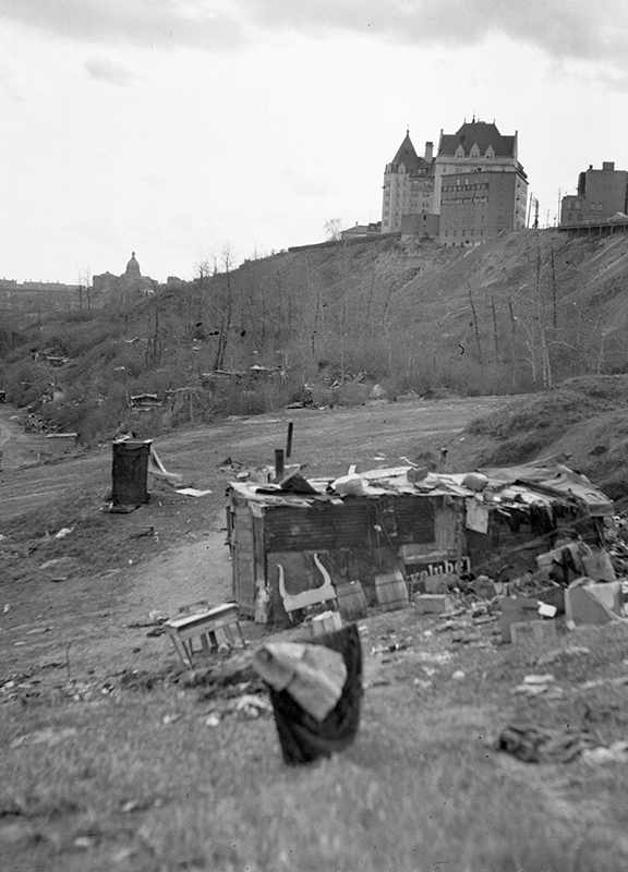 Image of the Grierson Dump with the Hotel MacDonald and the Alberta Legislature in the background, circa 1938. A small scavenged dwelling can be seen in the foreground of the image. Photo courtesy of the City of Edmonton Archives EA-160-325.