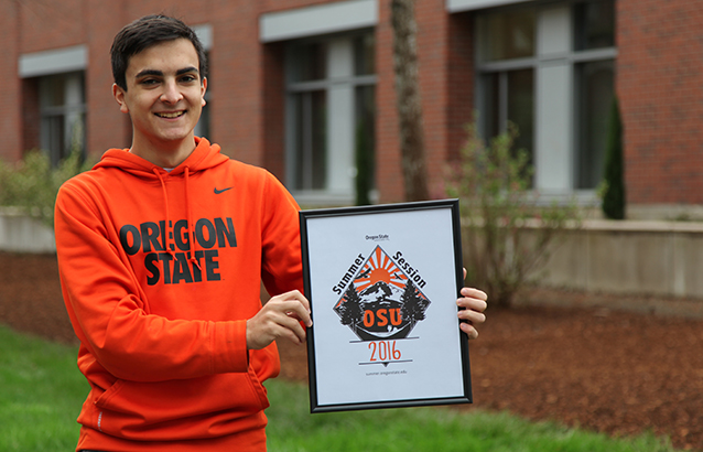 Francisco Boschetti Tofano, holds up his framed winning design for the 2016 Summer Session t-shirt design contest. He wears a bright orange Oregon State sweatshirt.