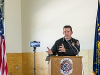 Executive Master of Public Policy student Bob Horton stands at a podium to give a speech in his role as fire chief in White City, Oregon. The flags of the United States and the state of Oregon are on either side of him.