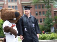 "Chris Holt wears his black graduation cap and gown and a black stole that reads ""Class of 2018"" and has the Oregon State University logo. To the left of Chris is Benny the Beaver, wearing a white Beavers jersey. Benny has one arm around Chris' shoulder as the two walk side by side."