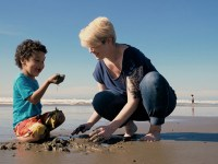 Oregon State Ecampus psychology student Christiania Jefferies plays in the damp sand with her son at a beach near their hometown of Tillmook, Oregon.