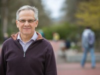 Dan Miles on the Oregon State campus. He wears a button-up shirt and a quarter-zip sweater.