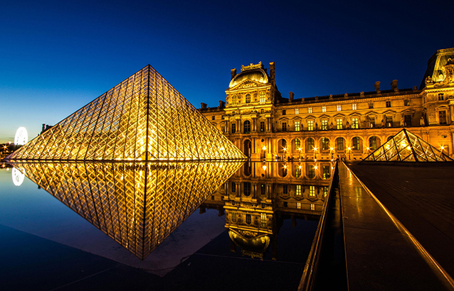 The Louvre Museum in Paris, France glows gold against a dark blue night sky.