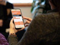 A person uses a smartphone to access Oregon State University's mental health resources online