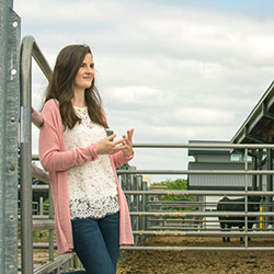 Grace Masterjohn stands in front of a metal gate and a black cow stands in the background. Grace faces slightly to the right and gestures with her hands.
