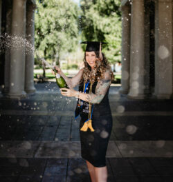 Hannah Thelen celebrates her graduation in a cap, stole and tassel, popping a bottle of sparkling grape juice.