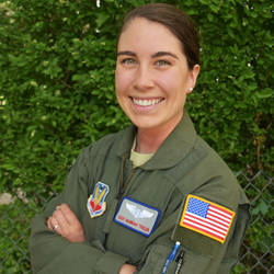 Hannah Thelen wearing a solid green Air Force uniform with patches on it, including an American flag on her left upper arm.