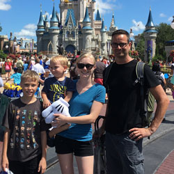 Oregon State Ecampus alumna Rachel Hensley poses with her family in front of a Disneyland castle.