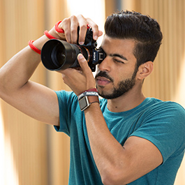 Hussain Al Balushi looks into his camera's viewfinder while taking a picture.