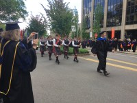 People walk through the streets on campus in the procession to Reser Stadium on graduation day.
