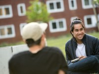 Two people sit outside on a campus lawn.
