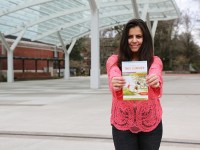 Isadora Costa Cardoso smiles and holds an OSU Summer Session brochure in front of her in the Student Experience Center plaza.