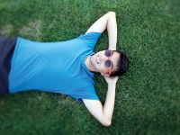 Oregon State student Jason Hsu lays on a lawn, relaxing with his hands behind his head.