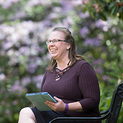 Women, gender and sexuality studies student Jennifer Oliphant sits on a black metal bench near a flowering bush and holds a tablet in her hands.