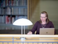 Jennifer Oliphant, a student in Oregon State University's women, gender and sexuality studies program, sits at a desk with a silver laptop open in front of her. She is writing in a notebook to the right of the laptop. In the room, there are several tall bookshelves and a bright white lamp.