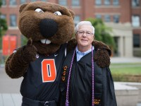 Oregon State's oldest 2017 graduate, Jerry Kight, poses with Benny the Beaver on graduation day.