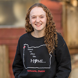 "Ecampus student Kalli Swanson wears a sweatshirt that says ""There's no place like home"" with an outline of the state of Oregon and a swirling tornado."