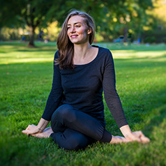 Katelin Gallagher, who teaches yoga and relaxation classes online at Oregon State Ecampus, sits on grass with her legs crossed tightly in a lotus pose.