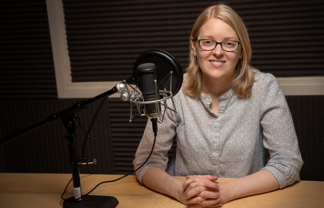 Katie Linder smiles with her hands resting on the table in front of her with her fingers interlocked. On the table is a black microphone with a pop filter.
