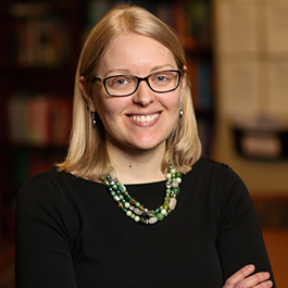 Oregon State Ecampus Research Director Katie Linder, Ph.D., poses smiling with arms crossed.