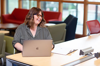 Oregon State Ecampus liberal studies student, Janine Romero, uses a silver laptop at a desk in a room with colorful sofas.
