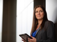 Lisa Frasieur, OSU Ecampus business administration graduate, holds a black tablet in an office-like setting.