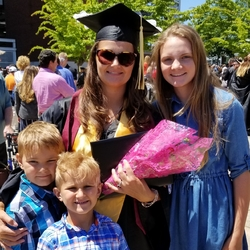 Maria Carpenter at Oregon State's Corvallis campus celebrating her graduation with her three kids smiling by her side. Maria wears her cap and gown, a yellow stole and black sunglasses and holds a bouquet of flowers wrapped in pink paper.
