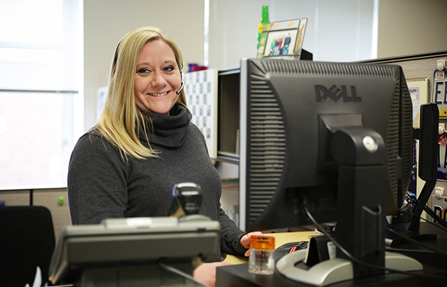 Melissa Whitney, an Ecampus enrollment services specialist, sits in front of her desk computer smiling and wearing a headset.