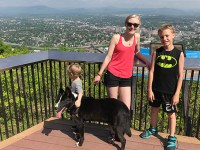 Ecampus anthropology alumna Rachel Hensley poses on a balcony with her two children and a black dog that she holds on a leash.